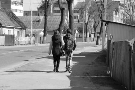 rapprochement: pair of young boy and girl fall in love walk on street in spring day
