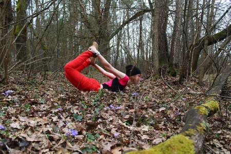 elongacion: hermoso arco mujer joven hecho de yoga asana (Dxanyrasana) en el bosque ma�ana de primavera