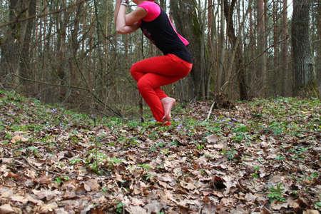 elongacion: Mujer joven hermosa hecha de yoga asana piernas retorcidas y manos (Garudasana) en el bosque ma�ana de primavera