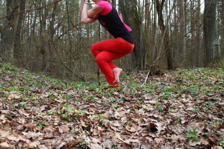 elongation: young beautiful woman made yoga asana twisted legs and hands ( Garudasana) in spring morning forest