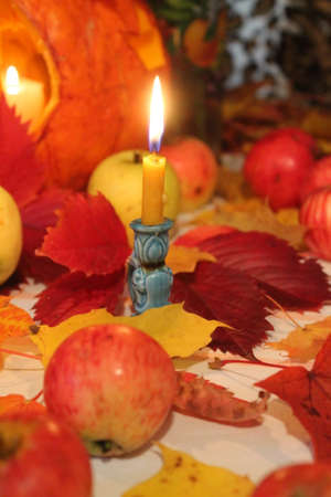 wax burning candle stay on ginger bright autumn leaves with red sweet apples nice decor for home