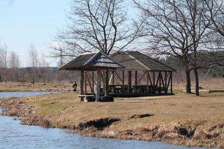 wooden stick: beautiful wooden summerhouse stay on bank of the deep blue river in grove in spring sunny day nice place for fishing and rest