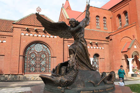 bronze statue of Saint Archangel Michel kill snack stay  near catholic church  Simona and Elena on square, Minsk, May, 2015, Belarus