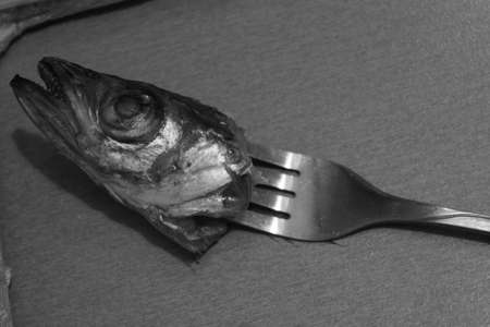 cut head of marine fish pick on the fork art and food in daily life