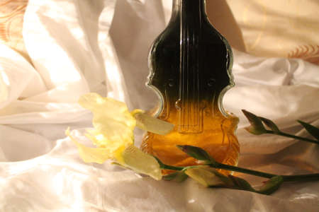 wine in crystal bottle in shape of violin and yellow iris decoration for evening romantic dinner Stock Photo