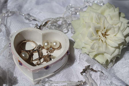 beautiful accessories from pearls in box shape of the heart and white pure rose prepare for wedding