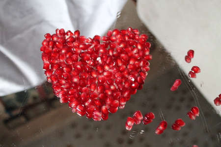 beautiful deep red colorf heart from ripe grain of sweet pomegrante fruit gift of love Stock Photo