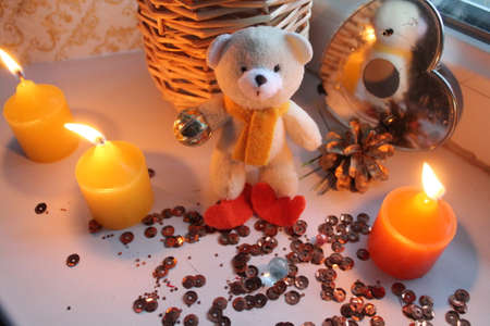 beautiful little terry teddy bear with three burn yellow candles decoration and gift on holiday
