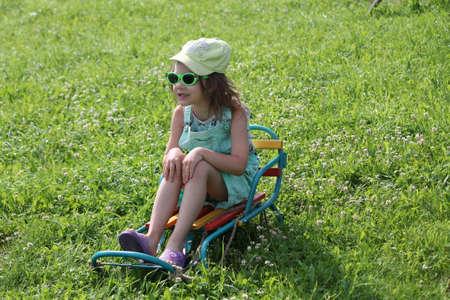 little girl on slide on the green grass Imagens