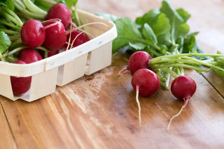 Garden radishes on the wet wooden table.