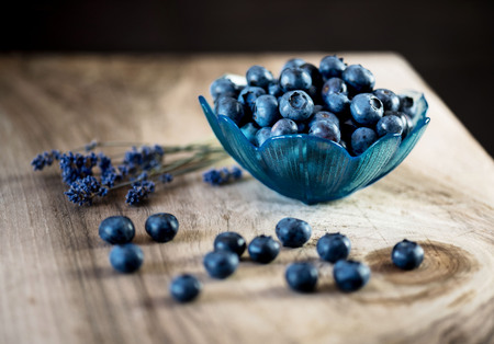 Blueberries in a bowl on a wooden table.