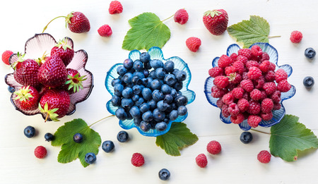 Different summer berries in glass bowls.