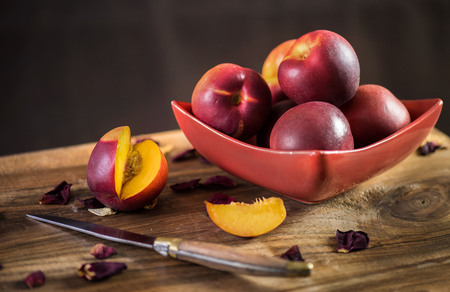 Ripe nectarines in a red plate. Rustic style. 版權商用圖片