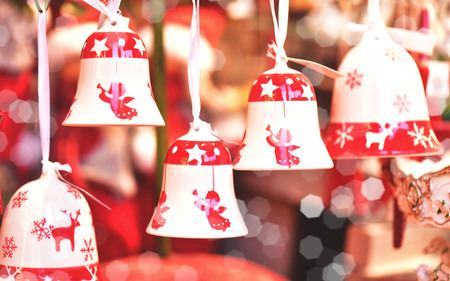 Porcelain bells with painted angels at the Christmas market. A gift for a Christmas holiday. Stock Photo