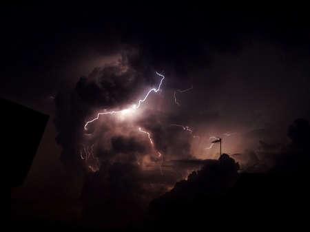 Fulmine nel cielo scuro e nuvoloso, con profilo del tetto Archivio Fotografico