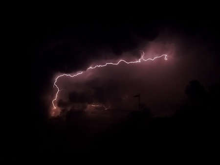 Lightning in dark and cloudy sky with purple colorshades   photo