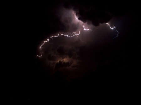 Lightning in dark and cloudy sky with purple colorshades
