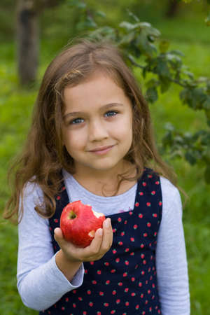 Cute Beautiful Russian Six-Year Girl Hold In Her Hand Fresh Ripe Tasty Red Eating An Apple, Smiling And Looking At Camera, Outdoor Close Up. Little Girl And Red Apple. Healthy Food.