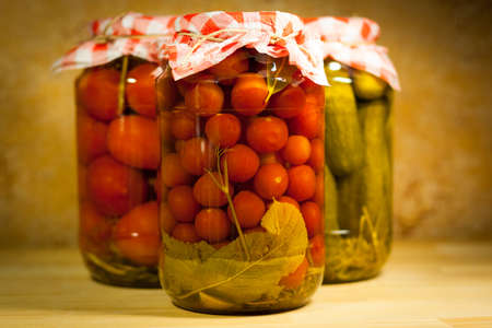 Homemade Canneds Vegetables. Close Up Of Tomatoes Cherry In Glass Jar On Background Indoor.