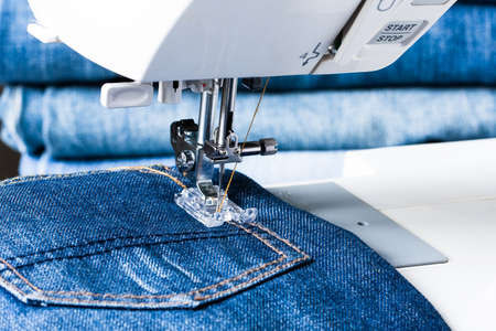 Sewing Jeans. Foot Of Sewing Machine On Jeans Fabric Close Up.