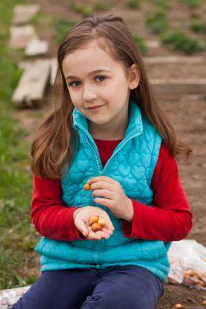 Cute Little Russian Seven Years Girl With Onion On Her Hand In Spring Garden. Preparing Onion-Seedling To Planting In Spring. Foto de archivo - 104871140