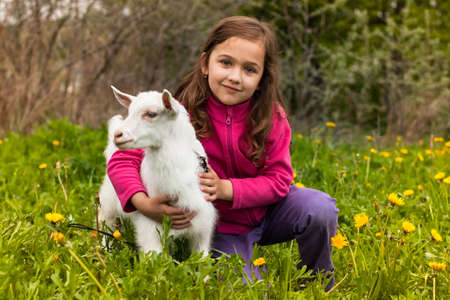 Portrait Of Beautiful Happy Little Girl Embracing Little Favorite Goat On Grass In Spring Garden.