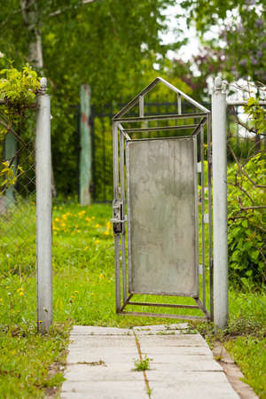Opened Old Painted Metal Gray Gate In Small Rainy Garden Spring Day. Stock Photo