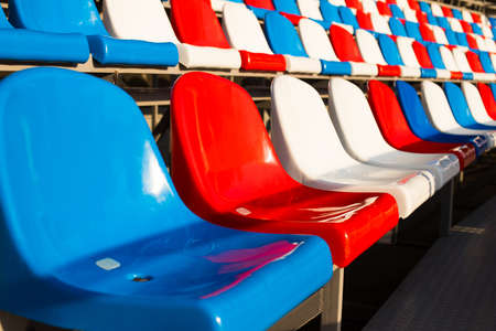 Empty Plastic Chairs In Stadium At Sunset Or At Sunrise Outdoor Close Up.
