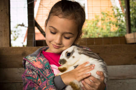 Rabbit. Cute Little Girl Holding In Her Embrace Cute Rabbit. Girl Playing With White, Grey Rabbit Indoor. Children Feeding Animal. Family With Animals. Stock fotó