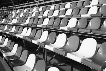 Empty Plastic Chairs In Stadium In Sunny Day Outdoor Close Up. Black And White Photo.