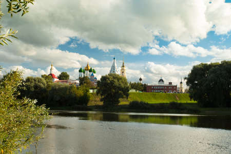 Kolomna, Moscow Region. Beautiful Landscape Of Various Temples And Belltower On Assumption Cathedral Square Under Blue Sky With Dramatic Clouds By Embankment Reflection River In Sunny Summer Day.