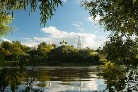 Beautiful Landscape Of Temples And Belltower On Assumption Cathedral Square Under Blue Sky With Dramatic Clouds By Embankment River In Sunny Summer Day In Kolomna, Moscow Region.