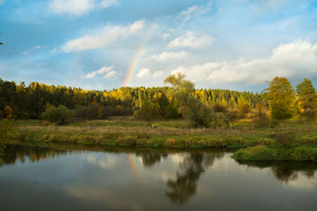 Autumn. Beautiful Bright Colorful Autumn Landscape With Rainbow On Blue Dramatic Sky And Reflected River. Stock fotó