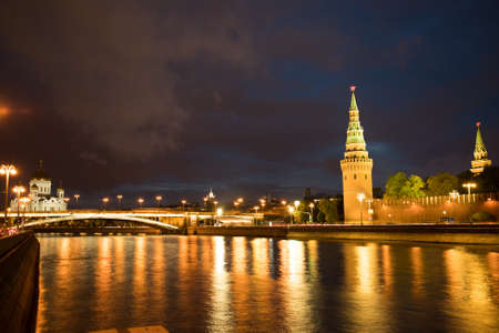 Moscow, Russia. Beautiful View Of Moscow Kremlin With Illumination And Big Stone Bridge By Moscow River With Reflection On Background Of Blue Hour With Clouds At Evening.