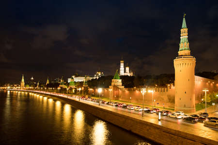 Moscow, Russia. Beautiful Landscape Night View On Moscow Kremlin With Cars On Road At Coast Of Moscow River With Reflection Of Illumination From Lamps In Autumn.