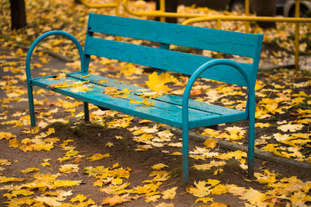 Autumn. Obsolete Wooden Bench Painted In Blue Color With Fallen Yellow Leaves In Autumn Park Outdoor. Stock fotó