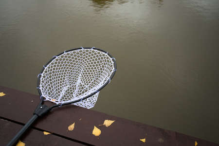 Fishing Net On Wooden Board Over Water Pond Autumn Copyspace And Top View.