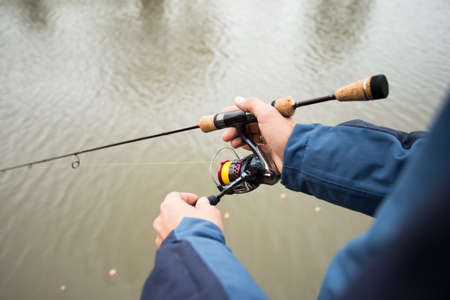 Activity Fisherman Male With Fishing Rod In His Hands On Fishing On Background Of Water Outdoors. Sport Fishing Hobby. Close Up.