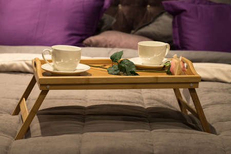 White Ceramic Cups With Rose Flower On Wooden Tray For Breakfast On Bed Close Up.