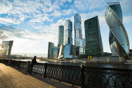 On Embankment Of Moskva River Man Male Looking Far At Modern Buildings Of Moscow City Complex Of Skyscrapers In Autumn Sunny Day. Stock fotó