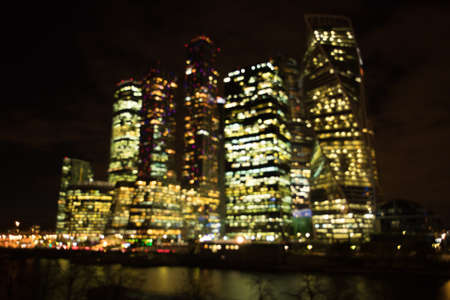 Blurred Background Of Business Center Of Moscow City Complex Of Skyscrapers By Moscow River Night.