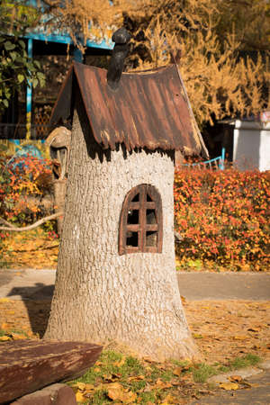 Toy Wooden House. Cute Decorative House From Tree Stump In Sunny Colorful Autumn Park.