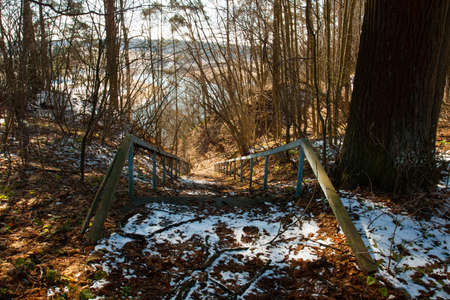 Old Iron Blue Staircase With Dry Leaves, Tree Branches And Snow Melts, Descending To River In Forest At Spring Top View.