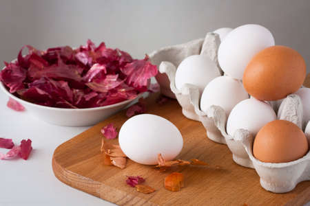 White And Brown Eggs On Wooden Cutting Board With Onion Peel On White Table At Easter.