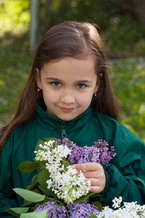 Cute Little Russian Girl With May Bouquet Of Lilac Flowers In Spring Garden Close up. Reklamní fotografie
