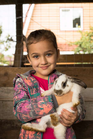 Rabbit. Happy Little Girl With Cute Rabbit In Her Embrace. Girl Playing With White, Grey Rabbit Indoor. Children Feeding Animal. Family With Animals. Stock Photo - 132239634