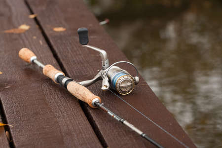 Fishing Rod On Wooden Pier On Pond On Fishing Outdoor Close Up.