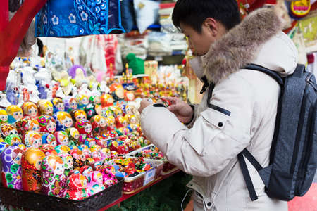 Moscow, Russia - December 21, 2017: Young Buyer Man Picks Toy Russian Nesting Doll (Matryoshka Dolls) In Shop On Red Square On Eve Of Feast Of New Year.