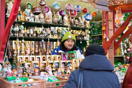 Moscow, Russia - December 21, 2017: Elderly Seller Man In Russian Toy Store On Red Square On Eve Of Feast Of New Year. 新聞圖片