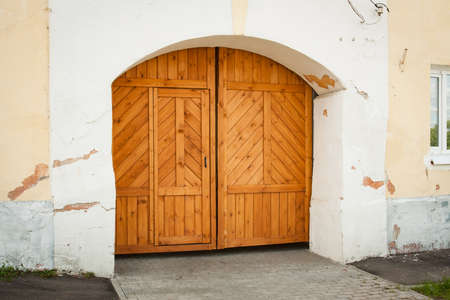 Classic Wooden Door Entrance With Arch In Old Stone Wall Of Residential Building. Background Texture.